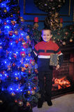 The boy next to a glowing blue Christmas tree and fireplace Royalty Free Stock Photos
