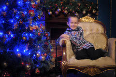 The boy next to a glowing blue Christmas tree and fireplace Stock Photo