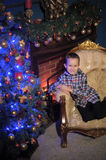 The boy next to a glowing blue Christmas tree and fireplace Royalty Free Stock Photography