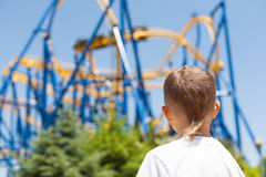 Boy next to a roller coaster Stock Photography