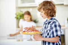 Boy nibbling from fresh fruit cake Royalty Free Stock Photo