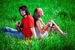 Boy and nice girl with wineglasses on grass Royalty Free Stock Photos