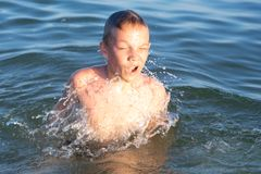 A boy of nine is swimming in the sea at sunset stock images