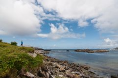 A boy and the norwegian west coastline. The vertical photo of the typical stone norwegian west coastline over blue sky royalty free stock photography
