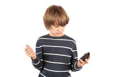 Boy not too happy with his basic mobile phone. Isolated on white. Boy not too happy with his basic mobile phone because it is not a smartphome. Isolated on white Royalty Free Stock Photo