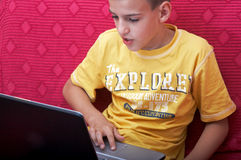 Boy with notebook. Little boy looking above laptop screen Stock Image