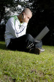Boy with notebook and cell phone in park Stock Photography