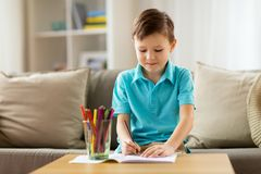 Boy with notebook and pencils drawing at home. Childhood, education, leisure and people concept - happy little boy with notebook and pencils drawing at home royalty free stock images