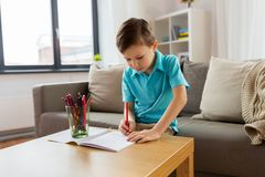 Boy with notebook and pencils drawing at home Stock Photos
