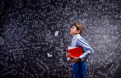 Boy with notebooks against big blackboard with mathematical symb Royalty Free Stock Images