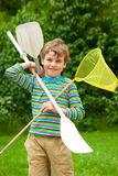 The boy with oars and a net outdoor. Summer Stock Photography