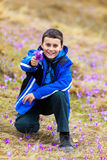 Boy offering a bunch of flowers. Portrait of a boy offering crocus flowers outdoor in a field Royalty Free Stock Photos