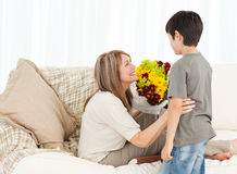 Boy offering flowers to his grandmother Stock Photo