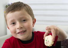 Boy offering you a chocolate cookie. Royalty Free Stock Image