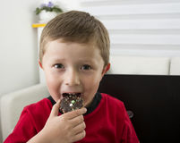 Boy offering you a chocolate cookie. Royalty Free Stock Photography