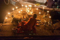 Boy with offerings to the Ganges. VARANASI, INDIA - 24 Oct 2016: A boy performs a religious ceremony to the Ganges on October 24, 2016 in Varanasi, India royalty free stock photos