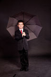 Boy in official dresscode with an umbrella Stock Images
