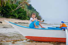 Boy in old boat on the beach Stock Photos