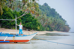 Boy in old boat on the beach Stock Image