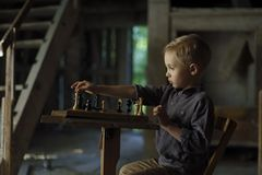 A boy in an old house is playing chess. stock image