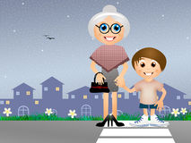 Boy with old lady in the crosswalk Royalty Free Stock Image