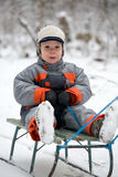 Boy on a old sledge. The boy in the winter suit sitting on a old sledge Royalty Free Stock Photography