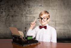 Boy with the old typewriter. Smiling boy with the old typewriter raising the index finger up. Retro style portrait Royalty Free Stock Image