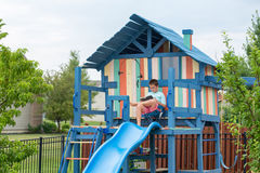 Free Boy On Chair Reading While Seated On Playhouse Royalty Free Stock Photo - 74027775