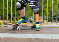 Boy with One Foot on Skateboard on Top of Ramp Stock Photography