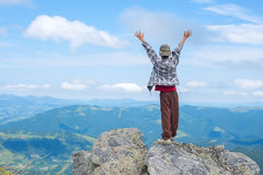 Boy with open arms stands on the cliff Royalty Free Stock Photos