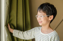 Boy open curtain and smile Stock Photo
