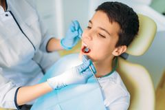 Boy with open mouth in a dental chair. Pediatric dentistry. The doctor examines the teeth of a small patient royalty free stock image