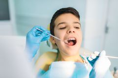 Boy with open mouth in a dental chair. Pediatric dentistry. The doctor examines the teeth of a small patient stock photos