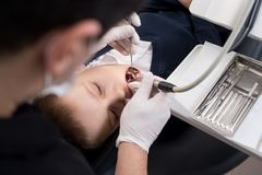 Boy with open mouth during drilling treatment at the pediatric dentist in dental clinic. Boy with open mouth during drilling treatment at pediatric dentist in Stock Images