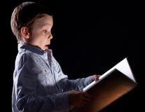 Boy opened a magic book Stock Photos