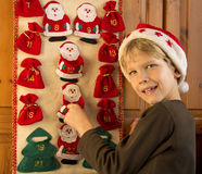 Boy opening Advent calendar. Cute boy with Santas hat opening Advent calendar Stock Photography