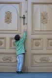 Boy opening the big door Stock Photography