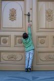 Boy opening the big door Stock Photos