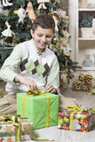 Boy is opening Christmas gifts Royalty Free Stock Photography