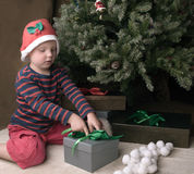 Boy is opening christmas present Royalty Free Stock Image