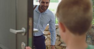 Boy opening the door and embracing his father in a comfortable home 4k. Rear view of Caucasian boy opening the door and embracing his father in a comfortable stock footage