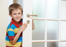 Boy opening door. Little smiling boy opening the white door at home Stock Photo