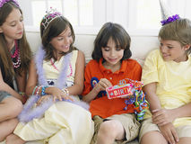 Boy Opening Gift With Guests At Party Royalty Free Stock Image