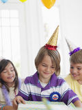 Boy Opening Gift With Guests At Party Stock Photos