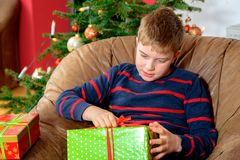 Boy is opening his christmas presents Royalty Free Stock Images
