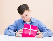 The boy opens a box of surprise. At the table Stock Images
