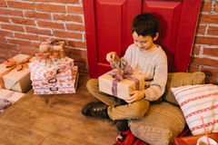 The boy opens a gift. Little boy opening gift for christmas, birthday Stock Photography