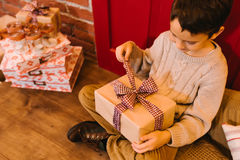 The boy opens a gift Stock Photography