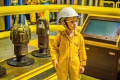 Boy operator recording operation of oil and gas process at oil and rig plant, offshore oil and gas industry, offshore. Oil and rig in the sea, operator monitor royalty free stock image