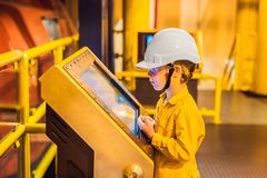 Boy operator recording operation of oil and gas process at oil and rig plant, offshore oil and gas industry, offshore. Oil and rig in the sea, operator monitor stock photo